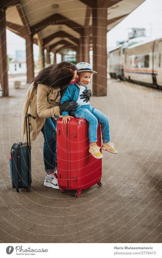 Mutter und Kind mit Gesichtsmaske und Gepäcktaschen warten am Bahnhof Erwachsener Tasche Taschen schön Kaukasier Großstadt Corona-Virus Covid-Reisen covid-19