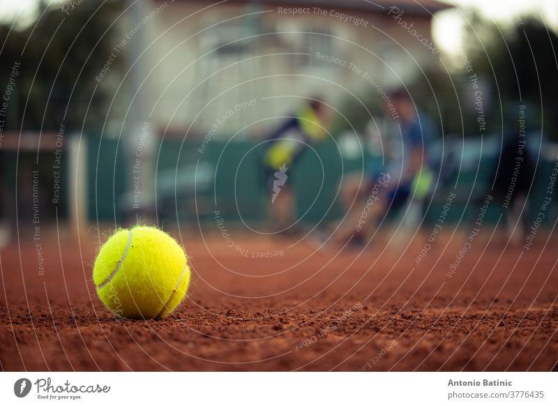 Nahaufnahme eines leuchtend gelben Tennisballs, der auf einem Spielfeld mit Sandplatz steht. Umrisse von zwei Personen im Hintergrund, Tennisspieler, die während einer Meisterschaft eine Pause machen
