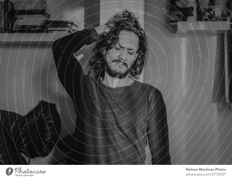Schwarzweiß-Porträt eines hispanischen Mannes. Er hat langes Haar und steht in einer Ecke des lebendigen Bräutigams. Latein Schwarzweißfoto Emotion cool Hypster
