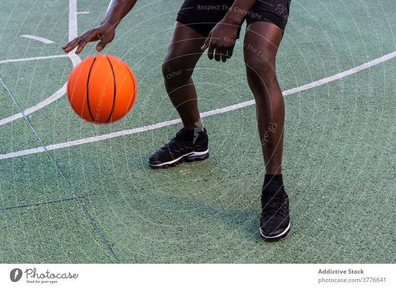 Konzentrierter schwarzer Mann spielt Basketball auf dem Platz Spieler spielen Ball Sportpark Spielplatz Taktik Fokus männlich Afroamerikaner ethnisch modern
