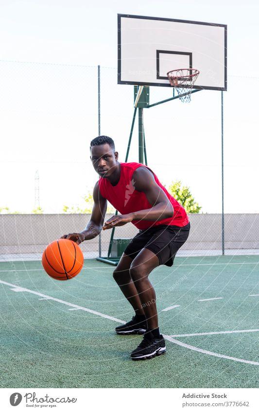 Konzentrierter schwarzer Mann spielt Basketball auf dem Platz Spieler spielen Ball Sportpark Spielplatz ernst Taktik Fokus männlich Afroamerikaner ethnisch