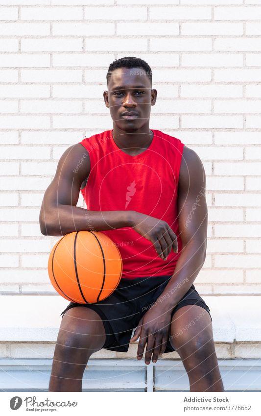 Ernster ethnischer Mann mit Basketball auf dem Platz Spieler Ball sich[Akk] entspannen Sportler Sportpark Spielplatz Stein Borte Bestimmen Sie männlich schwarz
