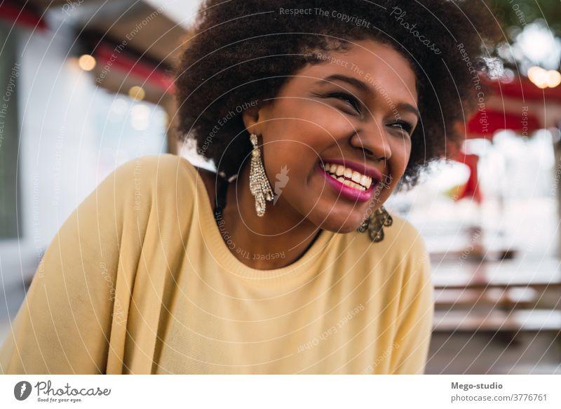 Afroamerikanische Lateinamerikanerin lächelt. Kaffeehaus Brasilianer schön Frau im Freien Café brünett krause Haare Freizeit Kunde selbstbewusst krauses Haar