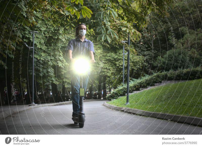 Maskierter junger Mann fährt umweltfreundlichen Elektroroller mit eingeschalteten Scheinwerfern im Park Tretroller Reiten Mitfahrgelegenheit Transport