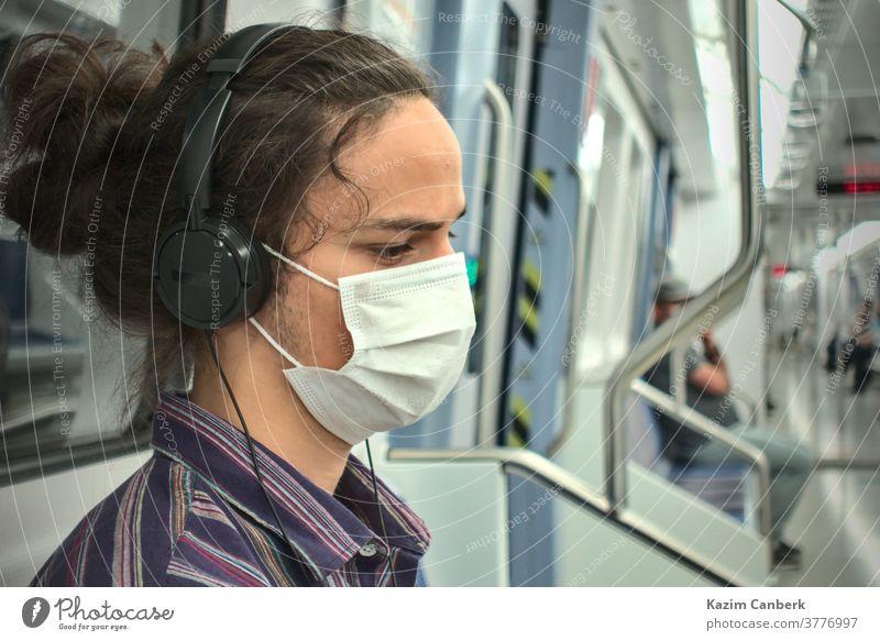 Maskierter, traurig aussehender Teenager, der in der U-Bahn mit Kopfhörern Musik hört unterirdisch Mundschutz Telefon Smartphone Sitzen Mann jung Schüler