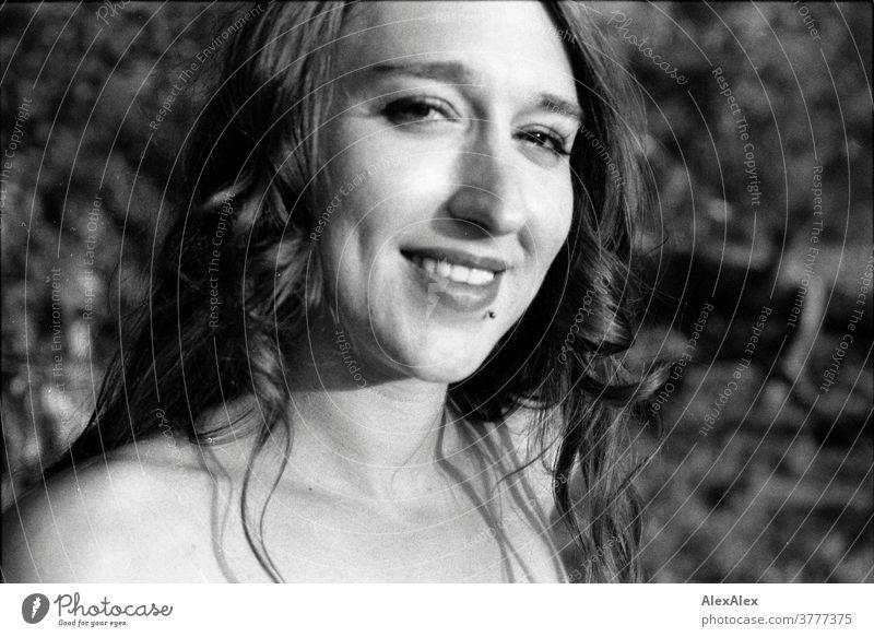 analoges, direktes, nahes Schwarz-Weiß-Portrait einer jungen Frau mit Wangengrübchen vor einem Strauch schön fit anmutig Haut nackt Gesicht Schultern blond