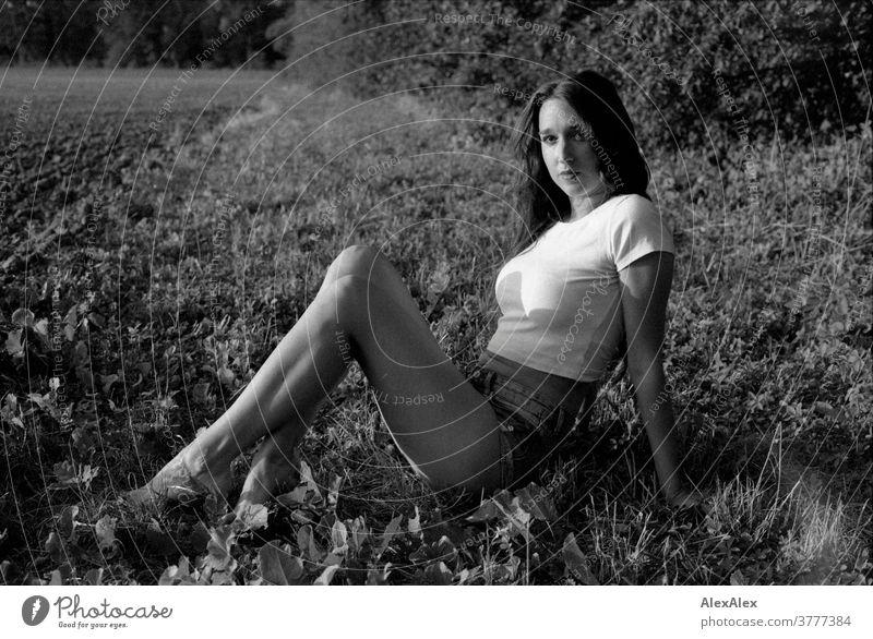 Schwarzweiß- Portrait einer jungen Frau, die vor einem Wald am Feldrand im Gras sitzt schön nah fit anmutig Haut Gesicht blond schauen direkt langhaarig schlank