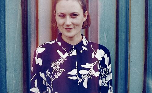 analoges, gecrosstes Portrait mit Fehlfarben einer jungen Frau vor einer rostigen Trapezblechwand junge Frau schön schlank Bluse Blumenmuster crossen
