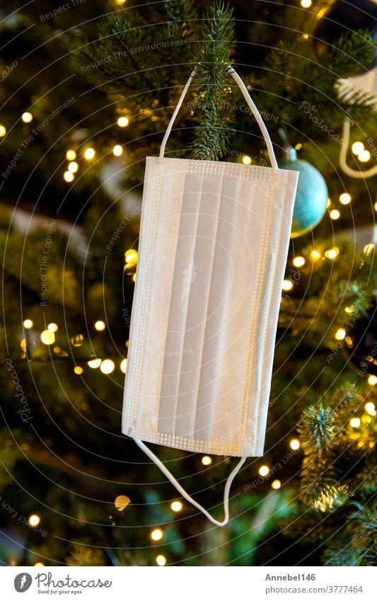 Weihnachtsbaum mit Coronavirus-Gesichtsmaske im Baum hängend, geschmückt mit Covid-19-Sicherheitsmaske und Weihnachtskugeln für strahlende Weihnachten Feier