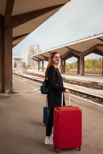 Frau mit Maske und Reisetasche wartet am öffentlichen Bahnhof Erwachsener attraktiv Tasche Gepäck schön Business Kaukasier Großstadt Coronavirus covid-19