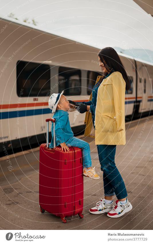 Mutter und Kind mit Gesichtsmaske und Gepäcktaschen, reisefertig Erwachsener Tasche Taschen schön Kaukasier Großstadt Corona-Virus Covid-Reisen covid-19