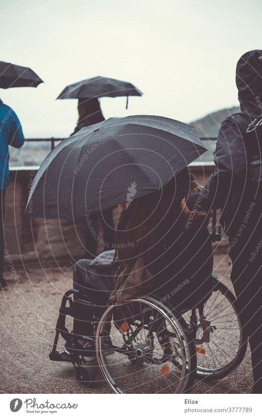 Ausflug mit Rollstuhl und Regenschirm weil es regnet und schlechtes Wetter ist. barierrefrei Aussicht Sightseeing Herbst nass Aussichtspunkt kalt regnerisch
