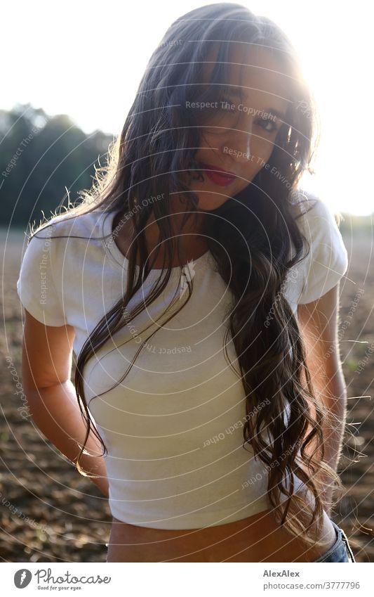 Gegenlicht- Portrait einer jungen Frau, die vor einem Feld steht und in die Kamera schaut schön nah fit anmutig Haut Gesicht blond schauen direkt langhaarig