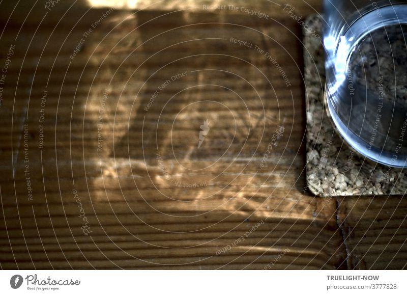 Ein Wasserglas mit Kork Untersetzer steht auf einem Holztisch und spiegelt und reflektiert das einfallende Sonnenlicht Sonnenschein Reflexion u. Spiegelung