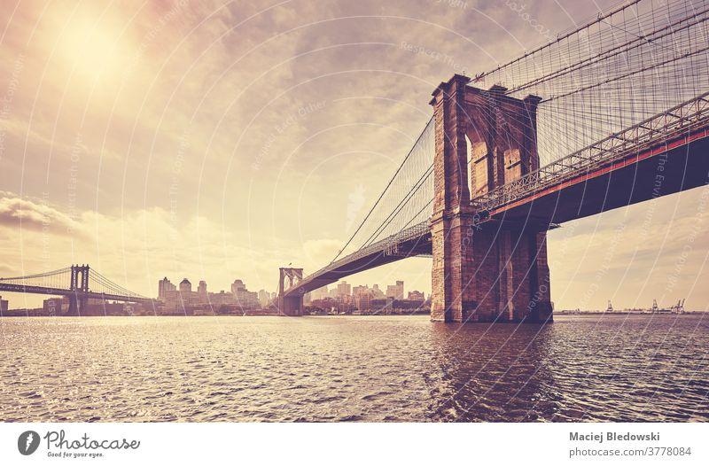 Vintage getöntes Bild der Brooklyn Bridge gegen die Sonne, New York. New York State Großstadt retro altehrwürdig Gebäude Stadtbild Sonnenuntergang Fluss Skyline