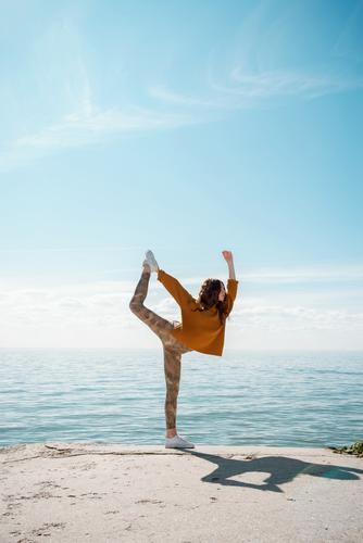 Junge Frau im Pullover am Strand beim Üben von Yoga Dancer's Pose (Natarajasana) yogini Straße cool Training Sportbekleidung Bewegung im Freien stylisch Hipster