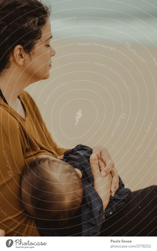 Mutter stillt Kleinkind am Strand stillen Krankenpflege Mutterschaft Mutter mit Kind Zusammensein Zusammengehörigkeitsgefühl Pflege Liebe Fröhlichkeit schön