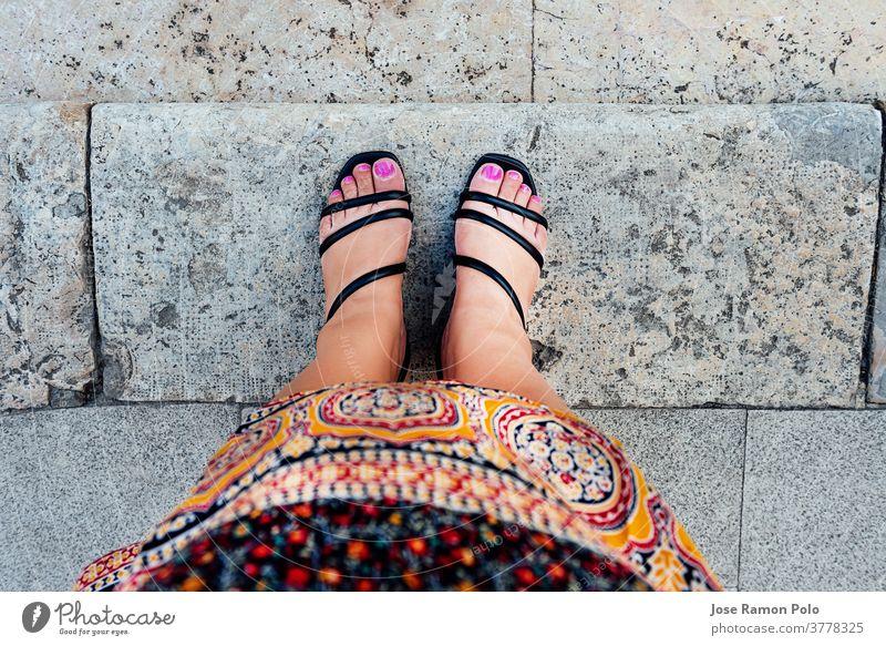 Frauenfüße in Ich-Perspektive mit fuchsiafarben lackierten Nägeln und schwarzen Schuhen, in marokkanischer Stammeskleidung, auf grauen Steinfliesen. ethnisches Konzept