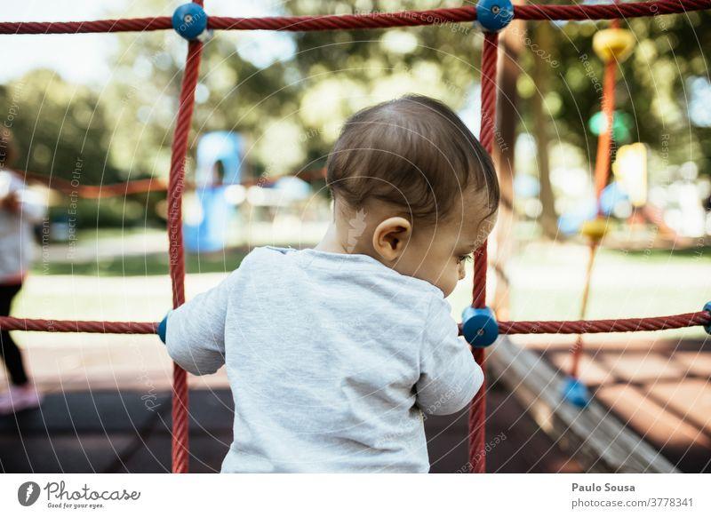Rückansicht eines auf dem Spielplatz spielenden Kindes Kindergarten Kleinkind Kindheit Kinderspiel Kindererziehung 1-3 Jahre Mensch Freizeit & Hobby Farbfoto