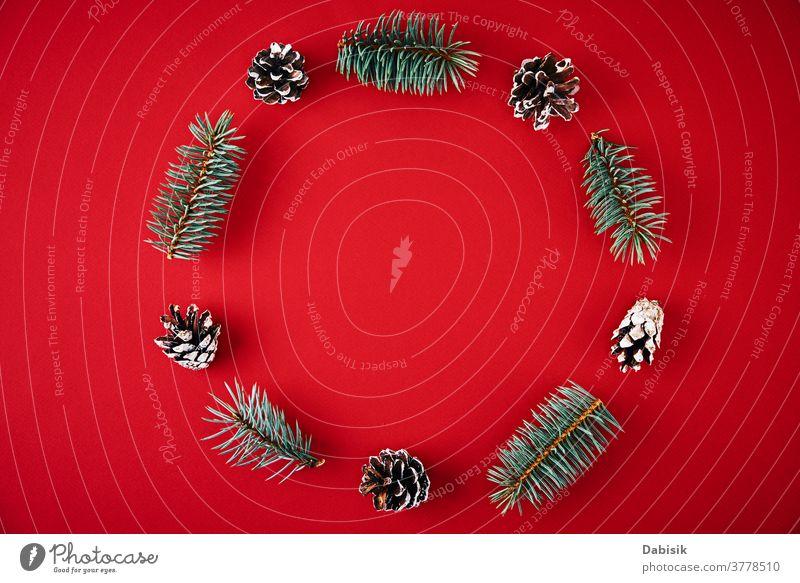 Weihnachtskomposition. Kranz aus Tannenbaumzweigen und festlichen Tannenzapfen auf rotem Hintergrund, Draufsicht Weihnachten Dekoration & Verzierung Totenkranz
