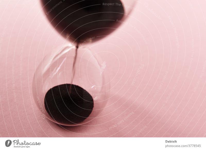 Sanduhr auf rosa Hintergrund, Nahaufnahme. Konzept Dringlichkeit und Zeitnot Uhr Glas Countdown altehrwürdig Aktion Stunde dringend Zeitschaltuhr Geduld Frist