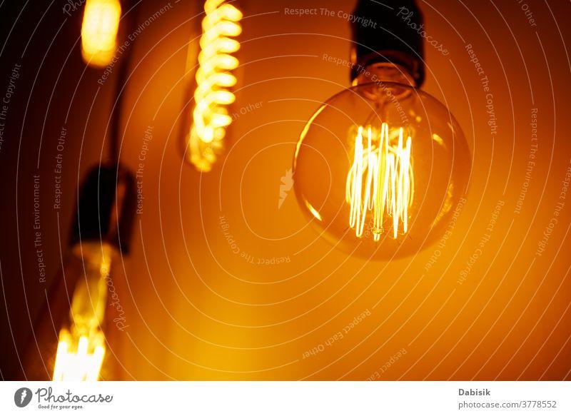Satz einer Vintage-Glühbirne auf orangem Hintergrund, Weichzeichner. Glühende Edison-Glühbirne Knolle Licht altehrwürdig Lampe Design weiß kreativ Konzept Idee