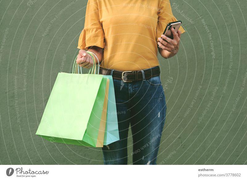 Frau, die eine Einkaufstasche und ein Smartphone in der Hand hält Junge Frau kaufen Frau beim Einkaufen Einkaufstaschen Werkstatt Käufer Lächeln Mädchen Spaß