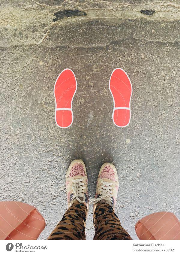 Schritte auf der Strasse in rot Vogelperspektive Schuhe Außenaufnahme Tag Fuß Beine Hose Farbfoto Bodenbelag Sneaker Fußabdruck; stehen Straße braun grau Stein