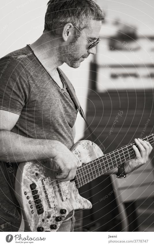 Bassist spielt voller Leidenschaft seine Bassgitarre Gitarre Musiker Klang Lied singen Musikinstrument Konzert hören Sputnik Leben fühlen genießen Ton Töne