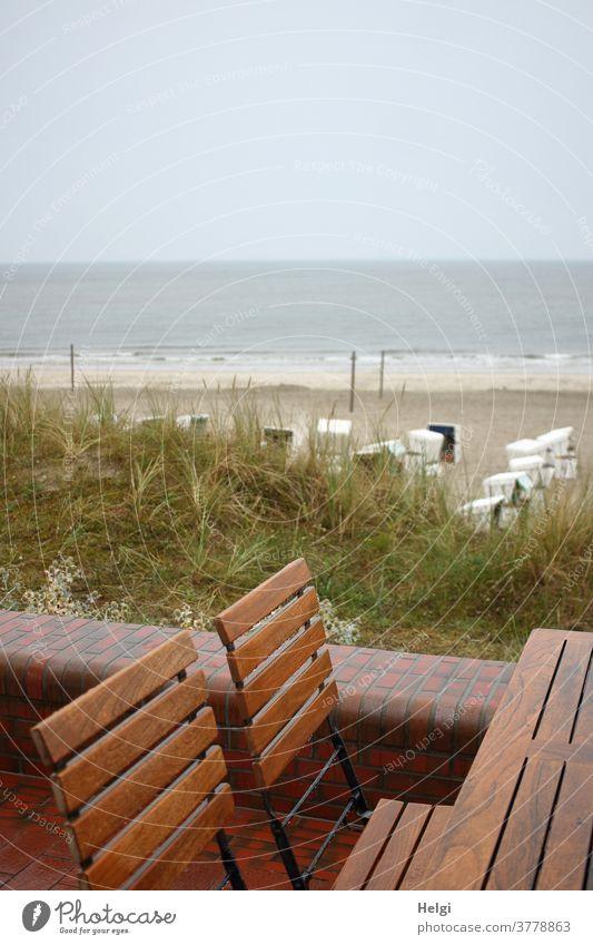 Regentag - leere nasse Stühle stehen am Tisch auf der Strandpromenade mit Blick auf den Strand mit Strandkörben und die rauhe Nordsee Düne Sand Wasser Meer