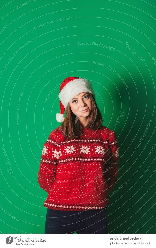 Junge Frau in Weihnachtspullover und Weihnachtsmannmütze auf grünem Hintergrund. Isoliert. Winter Chroma-Schlüssel Lächeln Feiertag Neujahr schön Schönheit