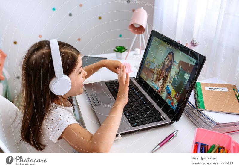Mädchen beobachtet Online-Klasse ihrer Lehrerin Heimunterricht Laptop winkend Online-Kurse digitale Weisheit Videokonferenz Videoanruf studierend Kopfhörer