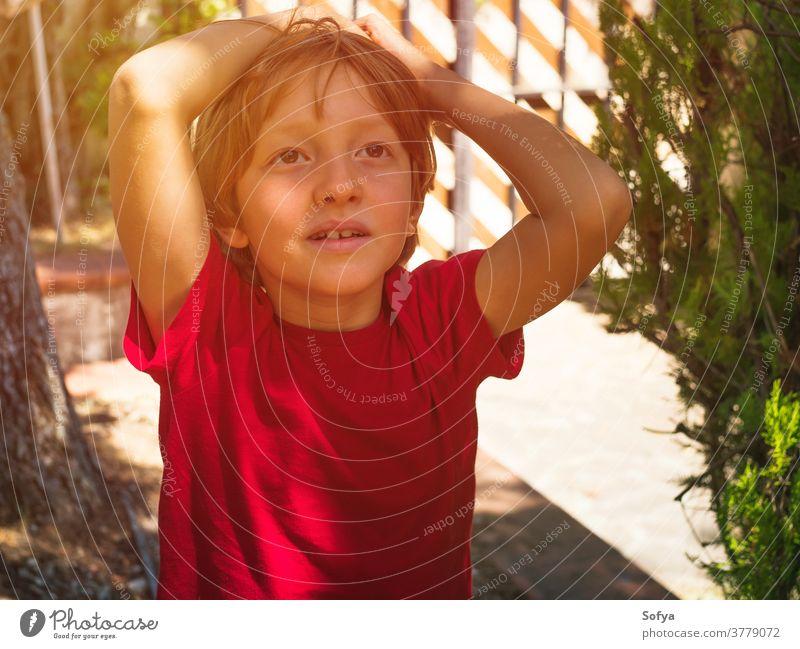 Kleiner Junge spielt im Sommer im Freien Lifestyle Kind authentisch Hinterhof Freiheit Natur Gesicht Lächeln Sonne Spaß wenig Porträt niedlich Freude blond