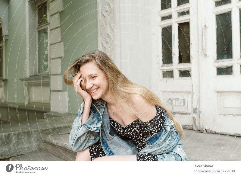 Porträt einer lachenden blonden Frau in Kleid und Jeansjacke, die im Freien sitzt Lächeln Menschen Lifestyle Glück Mädchen attraktiv freudig Kaukasier