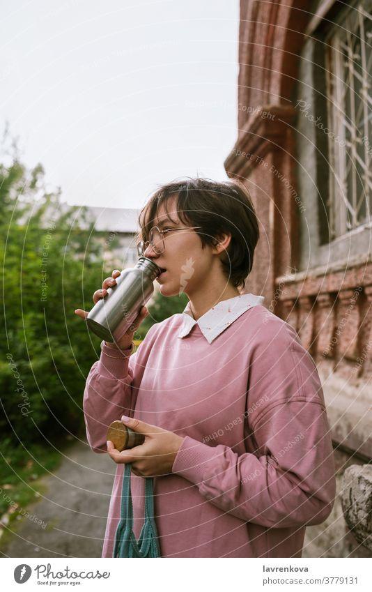 Junge erwachsene Frau mit kurzen Haaren trinkt aus Metall nachhaltiges Wasser im Freien, selektiver Fokus Flasche Hände Nahaufnahme Finger Beteiligung Mädchen