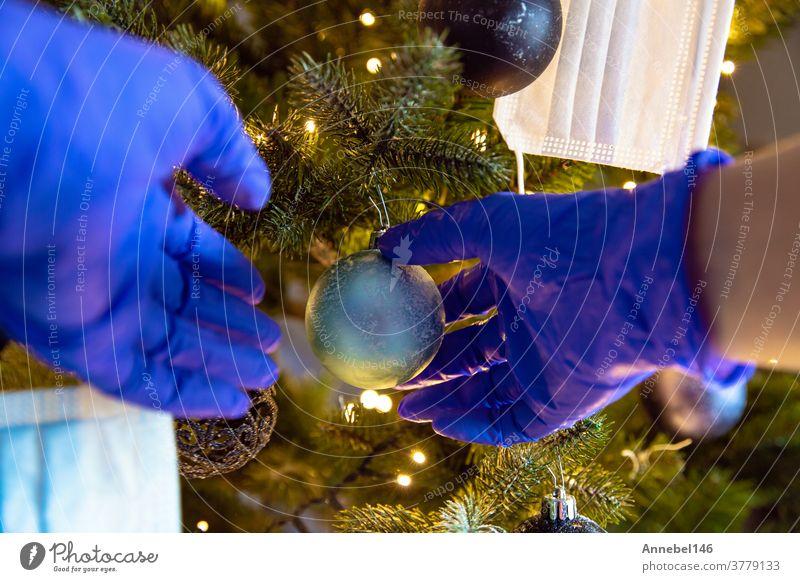 Person, die einen schönen Weihnachtsbaum mit Schutzhandschuhen für Covid-19 schmückt, Konzept für Coronavirus und Weihnachtsfeiertag erhängen Glück zu feiern