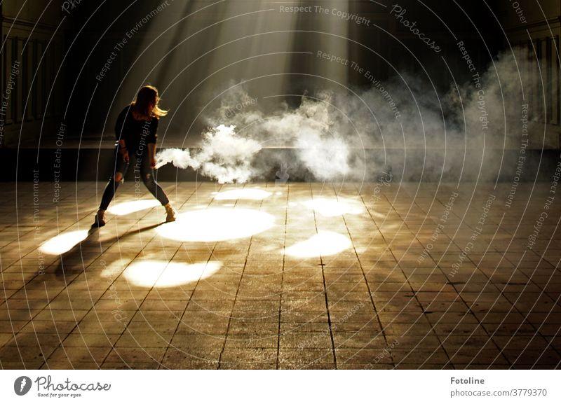 Die mit dem Rauch tanzt - oder eine junge Frau, die für Fotoline mit einer Rauchpatrone umhertanzt, um Sonnenstrahlen sichtbar zu machen Junge Frau Jugendliche