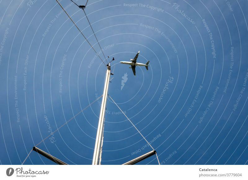Ein Flugzeug im Landeanflug, im Vordergrund ein Yachtmast, blauer Himmel aus der Froschperspektive Flugzeuglandung Luftverkehr fliegen Ferien & Urlaub & Reisen
