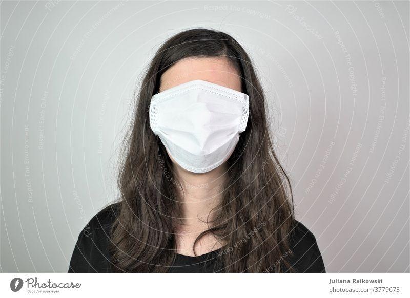 Frau mit Atemschutzmaske im Gesicht Kein Gesicht Mensch Maske Porträt Schutz atmen Kopf bedrohlich gefährlich coronavirus Angst Krankheit Infektionsgefahr