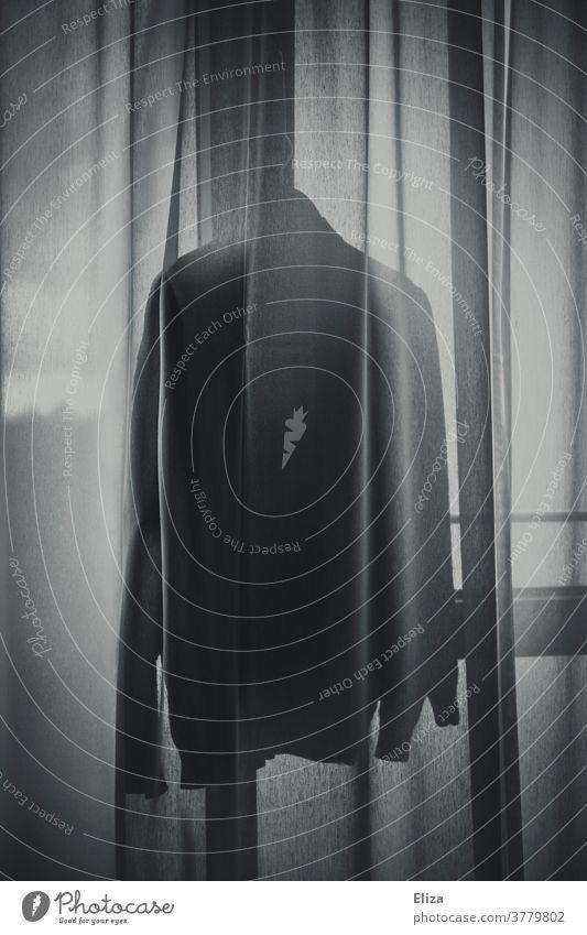 Ein Pullover hängt hinter einem Vorhang am Fenster im Licht Kleidung hängen pullover Bekleidung schemenhaft Silhouette Schatten Hemd Mode Gegenlicht anonym