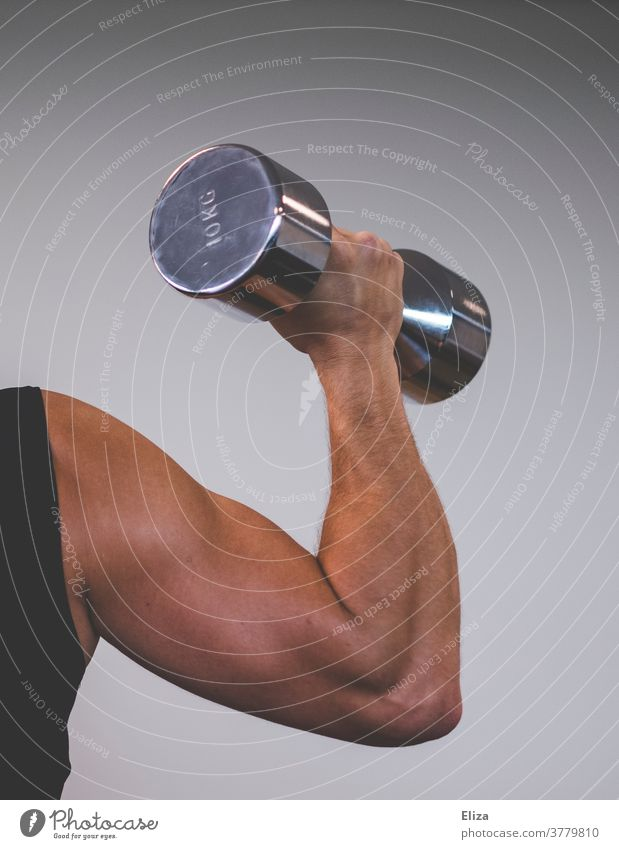 Ein muskulöser Mann mit trainierten Oberarmen stemmt eine 10 Kilo Hantel. Fokus auf dem Bizeps. stemmen Sport Kraftsport stark Körper Fitness Gewicht heben