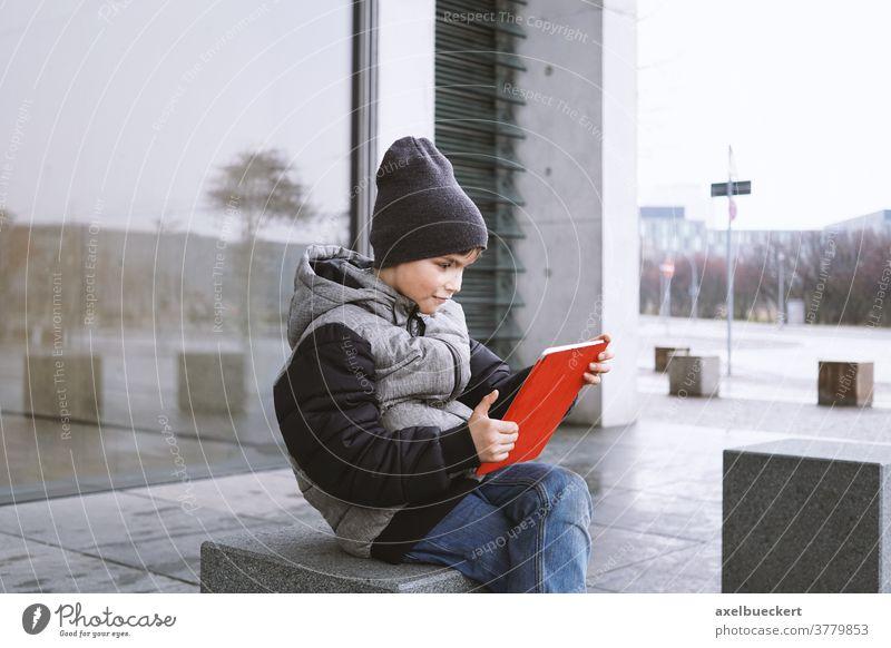7-jähriger Junge spielt im Winter Online-Spiel auf Tablet-Computer im Freien Kind Tablet Computer spielen Technik & Technologie digital jung Spaß Internet