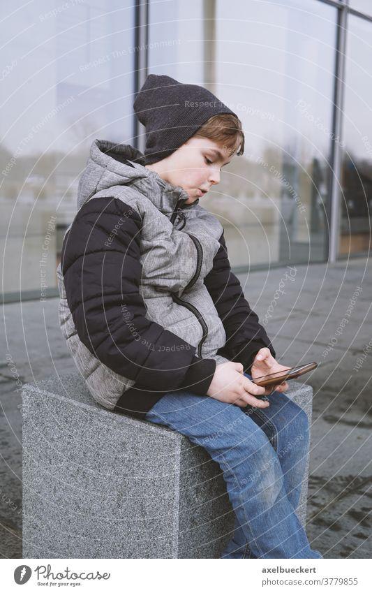 7-jähriger Junge spielt im Winter mit Smartphone im Freien Kind Handy Telefon Technik & Technologie spielen Spielen Menschen jung Internet Kindheit Lifestyle