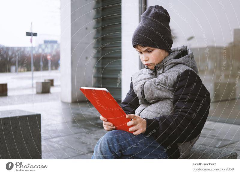 Junge schaut mit frustriertem Gesichtsausdruck auf Tablet-PC Kind tablet Computer Tablet Computer tablet-pc spielen Spiel Technik & Technologie Menschen digital