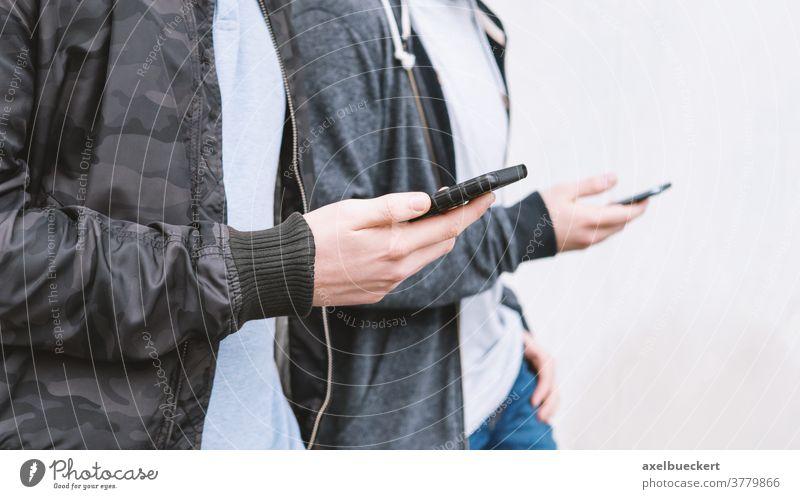 zwei männliche Teenager, die ein Smartphone benutzen Handy süchtig unsozial Telefon jung Männer Freunde benutzend Technik & Technologie Medien Netzwerk digital