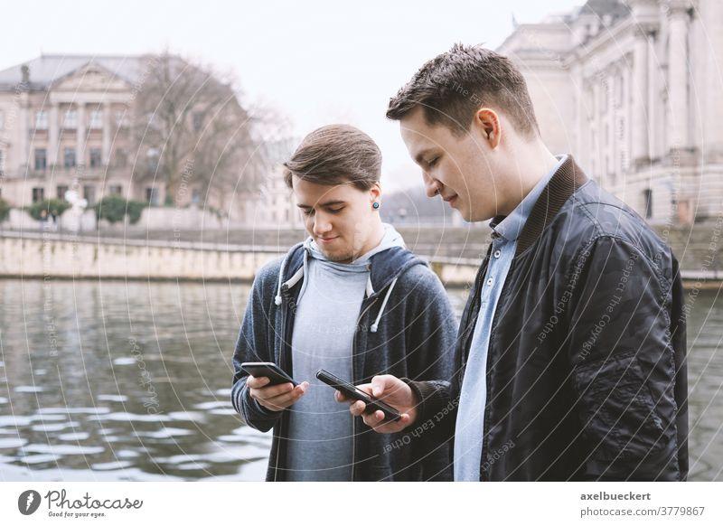 zwei smartphonesüchtige männliche Teenager stehen zusammen und schauen auf Handy Smartphone Abhängig Telefon unsozial jung Männer Freunde Technik & Technologie