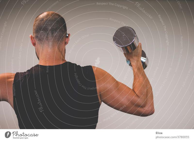 Ein muskulöser Mann mit trainiertem Bizeps stemmt eine 10 Kilo Hantel. stemmen Sport Kraftsport Oberarm stark Körper Fitness Gewicht heben sportlich Muskulatur