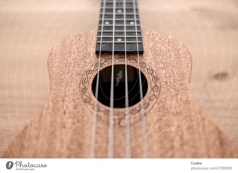 Braune Ukulele auf Holzgrund mit geringer Feldtiefe Instrument akustisch hölzern Musical Schnur braun Gitarre Musik Hintergrund Rosette hawaiianisch Objekt