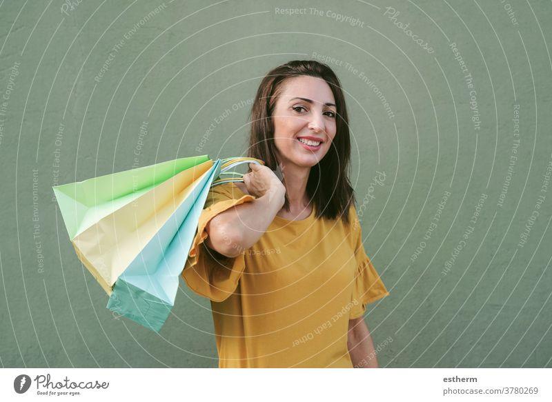 Lächelnde junge Frau, die eine Einkaufstasche hält Junge Frau kaufen Frau beim Einkaufen Einkaufstaschen Werkstatt Käufer Mädchen Spaß lustig Kaufhaus Gewerbe
