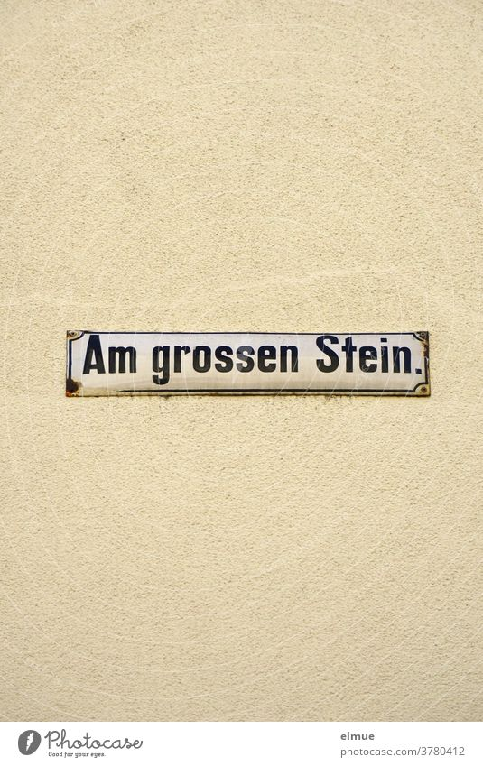 """Straßenschild """"Am großen Stein"""" an einer beigefarbenen Hauswand Straßenname Schild Wand Fassade Schrift Hinweisschild Adresse wohnen alt Putz"""